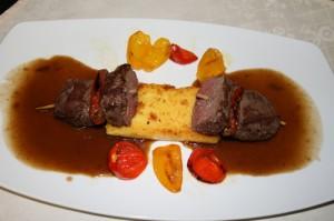 Spieß vom Gamsfilet dazu gebratene Polenta sowie rote und gelbe Babypaprika