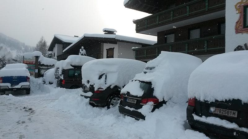Tief verschneite Autos vor dem Hotel Glockenstuhl in Westendorf