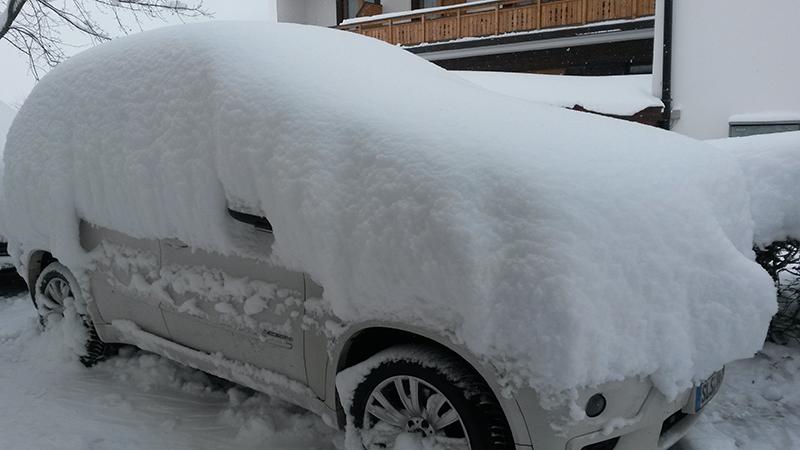 Tief verschneites Auto beim Hotel Glockenstuhl in Westendorf