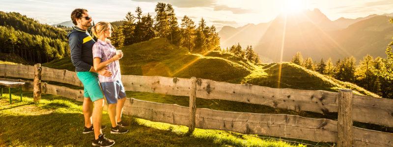 Mann und Frau genießen den Sonnenaufgang im Sommer in den Kitzbüheler Alpen